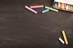 Mångfärgade färgrika färgpennor ligger på den svarta svart tavlan i klassrumskolahögskolan, kopieringsutrymme royaltyfri bild