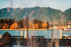 Mångfärgade färgstänk av vatten från en springbrunn mot backgen royaltyfri fotografi