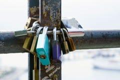 Mångfärgade förälskelselås som låsas på ett rostigt rör Symbol av förälskelse och lojalitet royaltyfri foto