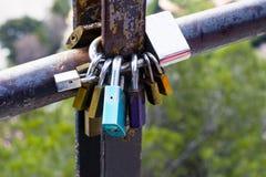 Mångfärgade förälskelselås som låsas på ett rostigt rör Symbol av förälskelse och lojalitet arkivfoton