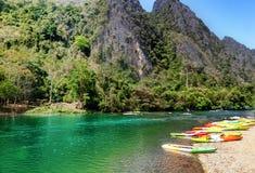 Mångfärgade fartyg för kayaking på kusten av en bergflod Arkivbild