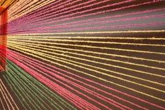 Mångfärgade garner fabriceras som den dekorativa gardinen som dekorerar byggnaden Fotografering för Bildbyråer