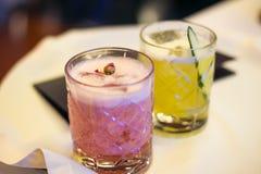 Mångfärgade icke-alkoholist coctailar i genomskinliga högväxta exponeringsglas royaltyfri fotografi