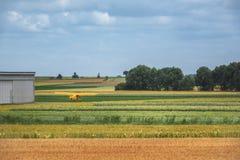 Mångfärgade jordbruks- fält och ett flygplan royaltyfri bild