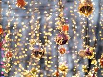 Mångfärgade julbollar på bakgrunden av brinnande girlander arkivfoto