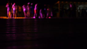 Mångfärgade ljus som vänder i nattklubben, när folket dansar suddigt stock video