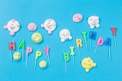 Mångfärgade marshmallower i form av små djur spridde på en blå bakgrund, en inskriftfödelsedag från arkivbild