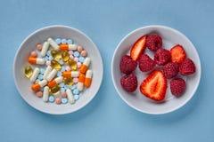 Mångfärgade minnestavlor och preventivpillerar, frukter och bär royaltyfria bilder