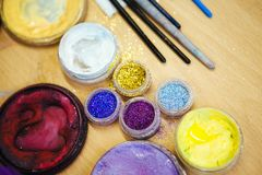 Mångfärgade paljetter i genomskinliga krus och makeupborste close upp arkivfoton