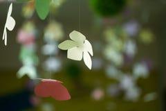 Mångfärgade pappers- blommor som är handgjorda på en abstrakt bakgrund Royaltyfri Foto