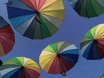 Mångfärgade paraplyer mot himlen i panelljuset Arkivfoton
