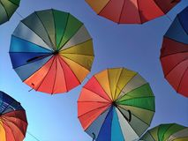 Mångfärgade paraplyer mot himlen i panelljuset Arkivbilder