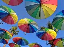 Mångfärgade paraplyer mot himlen i panelljuset Arkivfoto