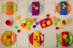 Mångfärgade plattor och linneservetter med den stack dekoren tabell royaltyfria bilder