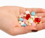 Mångfärgade preventivpillerar i den kvinnliga handen, närbild royaltyfria bilder