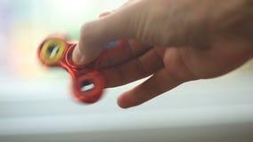 Mångfärgade räcker röd-guling-blått spinnaren eller den nervöst skruva på sig spinnaren som roterar på handen för man` s stock video