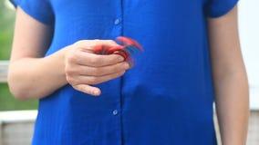 Mångfärgade räcker röd-guling-blått spinnaren eller den nervöst skruva på sig spinnaren som roterar på handen för man` s Kvinna s lager videofilmer