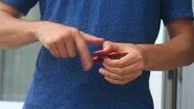 Mångfärgade räcker röd-guling-blått spinnaren eller den nervöst skruva på sig spinnaren som roterar på handen för man` s arkivfilmer