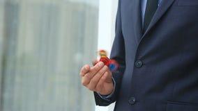 Mångfärgade räcker röd-guling-blått spinnaren eller den nervöst skruva på sig spinnaren som roterar på handen för man` s Man i en stock video