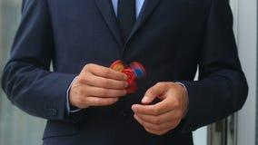 Mångfärgade räcker röd-guling-blått spinnaren eller den nervöst skruva på sig spinnaren som roterar på handen för man` s Man i en arkivfilmer