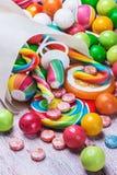 Mångfärgade sötsaker och tuggummi i pappers- påsar Arkivbilder