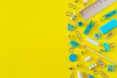 Mångfärgade skolatillförsel på gul bakgrund med kopieringsutrymme arkivfoto