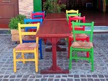 Mångfärgade stolar i den utomhus- grekiska restaurangen, Kreta, Grekland Royaltyfri Foto