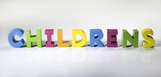 Mångfärgade textbarn som göras av trä. arkivbilder