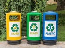 Mångfärgade tre återanvänder fack för avfalls med symboler för bekvämligheten av att sortera skräpavfalls i trädgården royaltyfri bild