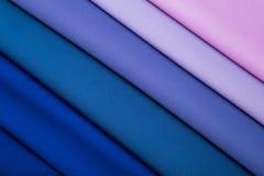 Mångfärgade veck av blått, lilan och rosa färgtyg royaltyfri foto