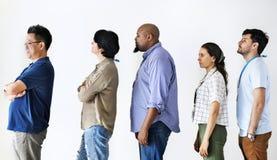 Mångfaldarbetare som tillsammans står i linje arkivfoton