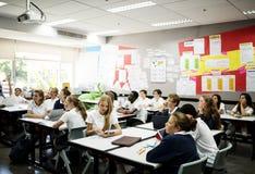 Mångfaldstudenter som lär i klassrumet arkivfoto