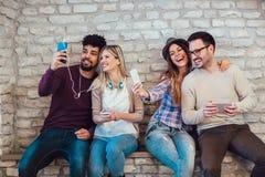 Mångfaldstudentvänner som använder Digital apparatbegrepp, fotografering för bildbyråer