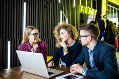 Mångfaldvänner som använder bärbar datorbegrepp på tabellen i modernt kafé royaltyfria bilder