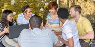 Mångkulturell grupp människor som diskuterar vid bärbara datorn royaltyfria bilder
