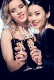 Mångkulturella flickor för glamour som rostar med champagneexponeringsglas på partiet Arkivbild