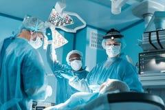 mångkulturella kirurger och patient under kirurgi Fotografering för Bildbyråer