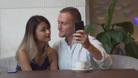 Mångkulturella par som tar självståenden genom att använda smartphonen Caucasian man, asiatisk kvinna arkivfilmer