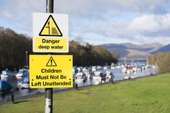 Måste barn för djupt vatten för fara inte lämnas det obevakade tecknet Loch Lomond UK Royaltyfri Foto