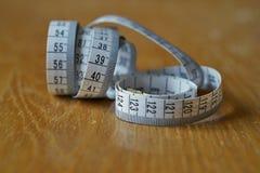 Måttband som mäter längd i cm och meter som används vanligt för att mäta omkretsen av människokroppen under matrisen fotografering för bildbyråer