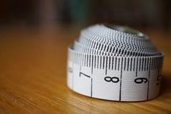 Måttband som mäter längd i cm och meter som används vanligt för att mäta omkretsen av människokroppen under matrisen arkivbilder