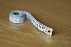 Måttband som mäter längd i cm och meter som används vanligt för att mäta omkretsen av människokroppen under matrisen Royaltyfri Foto