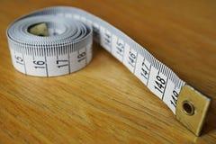 Måttband som mäter längd i cm och meter som används vanligt för att mäta omkretsen av människokroppen under matrisen royaltyfri fotografi