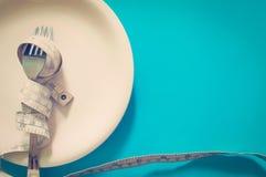 Måttbandet med gaffeln bantar begrepp Arkivbild