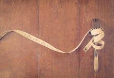 Måttbandet med gaffeln bantar concep Arkivfoto