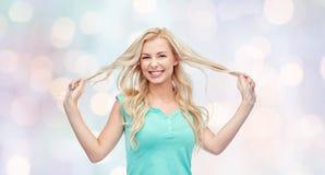 Mèche sorridenti della tenuta della giovane donna dei suoi capelli Immagini Stock