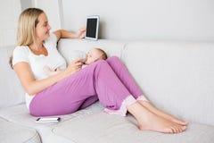 Mère à l'aide du comprimé numérique tout en alimentant son bébé avec la bouteille à lait Images libres de droits