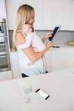 Mère à l'aide du comprimé numérique tout en portant son bébé dans la cuisine Image libre de droits