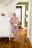 Mère à la maison portant la vieille chéri de sept mois Photos libres de droits