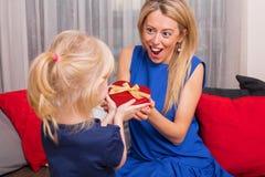 Mère étonnée au sujet de cadeau de filles Image libre de droits